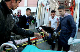 People help wounded a Syrian man in a Turkish hospital in Kilis,  southern Turkey after an  explosion near the border of Syria-Turkey in Es-Selame City, Feb. 20 , 2014.