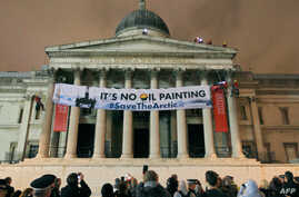 Greenpeace protesters scale the pillars of the National Gallery in central London, February 21, 2012, as they unfurl a banner in protest at oil firm Shell's plans for drilling oil in the Arctic region.