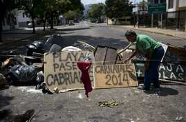 """Man arranges board with spraypainted message that reads""""Carnivals 2014,"""" at a barricade set up by anti-government protesters, Valencia, Venezuela, Feb. 27, 2014."""