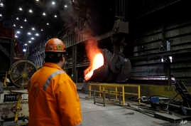 FILE- Senior melt operator Randy Feltmeyer watches a giant ladle backing away after pouring its contents of red-hot iron into a vessel in the basic oxygen furnace as part of the process of producing steel at the U.S. Steel Granite City Works facility