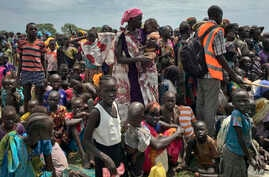 In this photo taken June 17, 2017, men, women and children line up to be registered with the World Food Program for food distribution in Old Fangak, in Jonglei state, one of the worst affected areas for food insecurity in South Sudan.