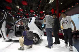 Visitors to Auto China 2016 take a closer look at Zotye Auto's E200 electric vehicle displayed in Beijing, Apr. 25, 2016.