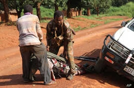 In this Monday, Sept. 16, 2013 photo, A Gabonese soldier from a regional Central African peacekeeping force helps collect the bodies of rebels who were reportedly killed by armed villagers in Njoh, Central African Republic.