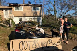 People stand near a sign warning looters in front of their house in Marianna, Florida, which was damaged by fallen trees during Hurricane Michael, Oct. 10, 2018.