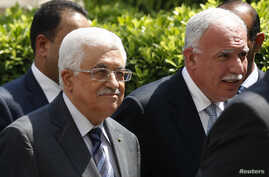 Palestinian President Mahmoud Abbas, left, and  his foreign minister, Riyad al-Maliki, right, arrive for an Arab League Foreign Ministers emergency meeting at the league's headquarters in Cairo, Egypt, Sept. 7, 2014.