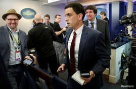 """Trey Yingst (center) of One American News Network and other journalists depart after an off camera """"gaggle"""" meeting with White House Press Secretary Sean Spicer while New York Times reporter Glen Thrush (left), who was excluded along with several oth"""