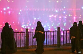 A Saudi woman takes photographs in a park during celebrations to mark the worldwide Earth Hour in Riyadh, Saudi Arabia, March 29, 2014.