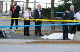 Authorities investigate the scene around a body covered under a white sheet next to a mangled bike along the bike path, Oct. 31, 2017, in New York.