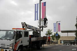 A worker installs decorations of Israeli and U.S. flags in front of the U.S. Consulate in Jerusalem which on Monday will formally be inaugurated as an embassy, in Jerusalem, May 7, 2018.
