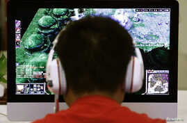 A man plays a computer game at an internet cafe in Beijing May 9, 2014. As growing numbers of young people in China immerse themselves in the cyber world, spending hours playing games online, worried parents are increasingly turning to boot camps to ...