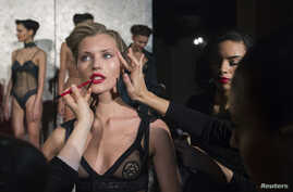 Make-up artists apply finishing touches to a model before a presentation of creations from the La Perla Autumn/Winter 2013 collection during New York Fashion Week in New York February 7, 2013.