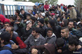 Migrants wait in front of a registration camp for migrants in Opatovac, Croatia, Sept. 22, 2015.