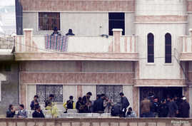 Members of the Free Syrian Army gather at a house in the northern Syrian town of Ras al-Ain, as seen from the Turkish border town of Ceylanpinar, Sanliurfa province, November 26, 2012.