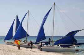 FILE - Tourists takes photographs along local sailboats on the island of Boracay, central Philippines, Jan. 18, 2016.