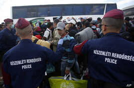 Hungarian police officers stop a group of migrants before a bus that would take the migrants in Roszke, southern Hungary, Sept. 8, 2015.