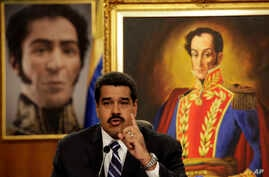 Between two portraits of Venezuela's hero Simon Bolivar in the background, President Nicolas Maduro speaks during a press conference in Caracas, Dec. 30, 2014.