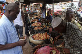 Food prices have shot up in the three countries most affected by Ebola, including Guinea. A customer shops at a market in its capital, Conakry, Aug. 15, 2014.