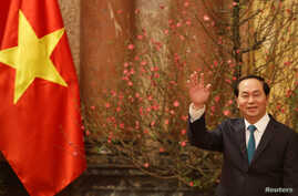 Vietnam's President Tran Dai Quang waves his hand to the media as he waits for arrival of Japan's Prime Minister Shinzo Abe at the Presidential Palace in Hanoi, Vietnam, Jan. 16, 2017.