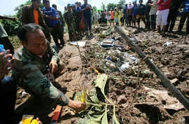 A Lao soldier places incense sticks into the ground beside the wreckage left by a Lao Airlines turboprop plane as he pays his respects to the victims of Wednesday's ill-fated flight, in Pakse, Laos, Oct. 17, 2013.