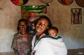 Mebrit Kasua and one of her children at her home in the Tigray Province of northern Ethiopia. Mebrit is a leader in the health development army of women in the Tigray province of northern Ethiopia.  The women fight trachoma by providing accurate educ