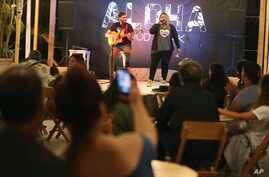 In this Jan. 12, 2019 photo, Venezuelan singer Reymar Perdomo performs with fellow Venezuelan and guitarist Omar Rumbos at a fair on the beach of San Bartolo, Peru.
