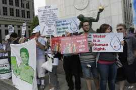 FILE - People stand outside Detroit City Hall, protesting thousands of residential water-service shutoffs by Detroit's water department, during a rally in Detroit, Thursday, July 24, 2014.