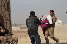 An Iraqi soldier carries a wounded girl into Mosul's only clinic for treatment before transport to a hospital on Nov. 27, 2016. (H. Murdock/VOA)