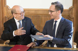 French foreign minister Jean-Yves Le Drian,  left, and his German counterpart Heiko Maas, exchange documents at Villa Borsig in Berlin, May 7, 2018.
