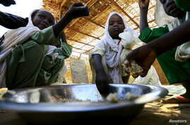Internally displaced schoolchildren eat from the same bowl during a feeding program provided by the World Food Program at the Abushouk camp in Al Fasher in North Darfur, Sudan, Nov. 17, 2015.