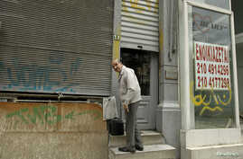 """A man prepares to leave his shop next to an empty one with a sign reading """"For Rent"""" in Piraeus port-town near Athens, May 29, 2012."""