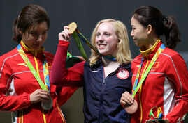 Virginia Thrasher, center, of the United States holds her gold medal for the Women's 10m Air Rifle competition during the award ceremony at the 2016 Summer Olympics in Rio de Janeiro, Brazil, Aug. 6, 2016.