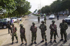 Nigerian army soldiers stand guard as they cordon off a road leading to the scene of a blast at a business district in Abuja, June 25, 2014.