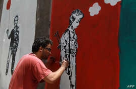 A Yemeni artist works on a mural as part of a campaign to end the recruitment of child soldiers by tribal militias in the capital Sana'a, April 10, 2014.