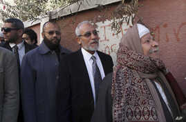 FILE - Muslim Brotherhood leader Mohammed Badie, second right, waits in line outside a polling place in Beni Suef, Egypt, to vote on a constitution drafted by Islamist supporters of President Mohammed Morsi.