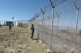 FILE - Pakistani soldiers stand guard at newly erected fence between Pakistan and Afghanistan at Angore Adda, Pakistan, Oct. 18, 2017.