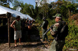 "FILE - Agents of the Brazilian Institute for the Environment and Renewable Natural Resources check a man at in illegal logging camp during ""Operation Green Wave,"" Aug. 21, 2017. Trusting that every effort will help to save rainforest, Environment Min"
