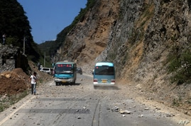 Two buses make their way across a road full of fallen rocks after a series of earthquakes, one of them measuring magnitude 5.7, hit the area near Zhaotong municipality at the border of southwest China's Yunnan and Guizhou province on September 7, 20