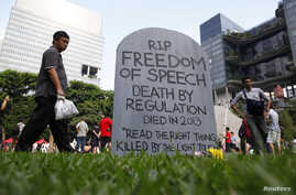 "FILE - Protesters walk past a mock gravestone that reads ""RIP Freedom of Speech"" during a protest against new licensing regulations imposed by the government for online news sites, at Hong Lim Park in Singapore."