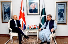 In this photo released by the Press Information Department, Pakistani Foreign Minister Shah Mahmood Qureshi, right, meets visiting British Home Secretary Sajid Javid at the Foreign Ministry in Islamabad, Pakistan, Monday, Sept. 17, 2018. Javid said M