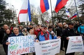 Pro-Russia demonstrators holding Russian and Crimean flags and posters rally in front of the local parliament building in Crimea's capital Simferopol, Ukraine, March 6, 2014.