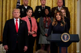 President Donald Trump listens as first lady Melania Trump speaks during an event on the opioid crisis, in the East Room of the White House, Oct. 24, 2018, in Washington.