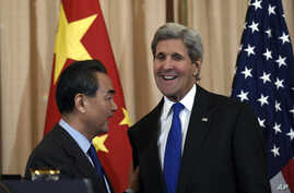 Secretary of State John Kerry talks with with Chinese Foreign Minister Wang Yi as they wrap up their news conference at the State Department in Washington, Feb. 23, 2016.