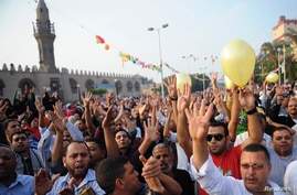 Members of the Muslim Brotherhood and supporters of ousted Egyptian President Mohamed Morsi shout slogans against the military and interior ministry as they gesture the number four, in front of Amr Ibn El-Aas mosque after Eid al-Adha prayers in Cairo