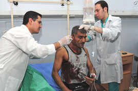 Syrian doctors treat an injured man who was wounded after two bombs exploded, at Qazaz neighborhood in Damascus, Syria, May 10, 2012.