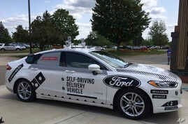 FILE - An Aug. 24, 2017, photo, shows the specially designed delivery car that Ford Motor Co. and Domino's Pizza will use to test self-driving pizza deliveries, at Domino's headquarters in Ann Arbor, Michigan.