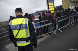 FILE - A police officer keeps guard as migrants arrive at Hyllie station outside Malmo, Sweden. Picture taken Nov. 19, 2015.