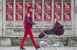 FILE - A woman pushes a stroller past posters advertising the Party of Communists of Moldova, in Chisinau, Moldova, May 28, 2015.