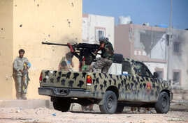 A member of Libyan forces allied with the U.N.-backed government fires a weapon on a pickup truck during a battle with Islamic State militants in Giza Bahreya, in Sirte, Libya, Oct. 27, 2016.