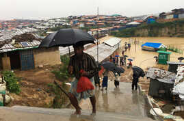 Rohingya refugees walks along the refugee camp during rain in Cox's Bazar, Bangladesh, July 25, 2018.