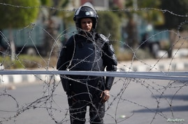 A police officer stands guard outside a police academy, where the trial of ousted Egyptian President Mohamed Mursi and members of the Muslim Brotherhood is due to take place, on the outskirts of Cairo, Feb. 1, 2014.